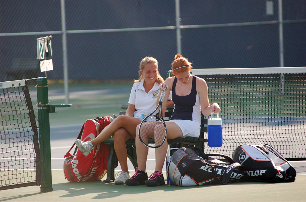 Head coach Cassie Lomison shares a coaching moment with sophomore Alyson O'Conner.