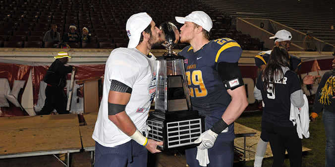 Juniors Garrett Isch and Jeremy Shupperd kiss the Dr. Tom Osborne Trophy as NAIA champions on Saturday night.